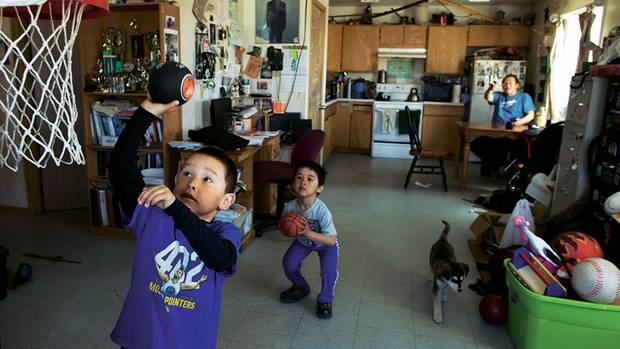 Merle Apassingok, ein Onkel von Chris, beobachtet seine Enkel zu Hause beim Spielen. Die meisten Familien leben in einfachen Holzhäusern