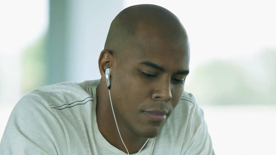 Ein junger Mann liest ein Buch mit Kopfhörern in den Ohren