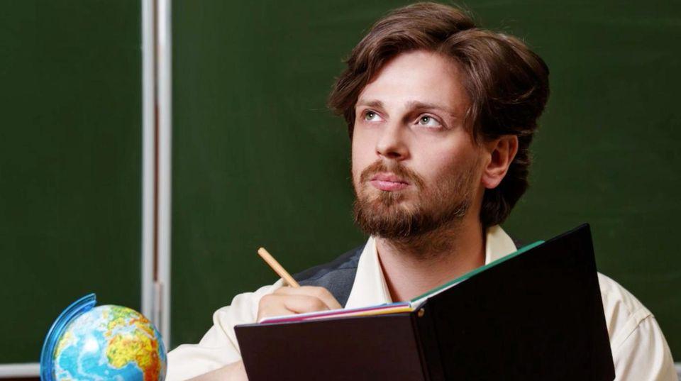 Mann sitzt an einem Lehrerpult vor einer Tafel