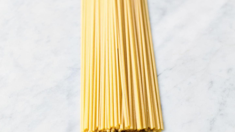 Die Pasta in kochendem Salzwasser nach Packungsangabe garen, dann abgießen und dabei einen Becher Kochwasser auffangen.