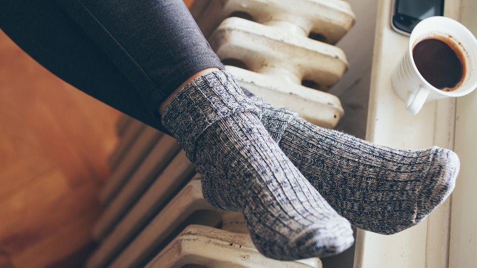 Die Füße einer Frau liegen in Wollsocken auf einer Heizung. Auf der Fensterbank stehen ein Kaffeebecher und ein Smartphone