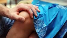 Die Hand eines Mannes am Knie einer Frau (Symbolbild)