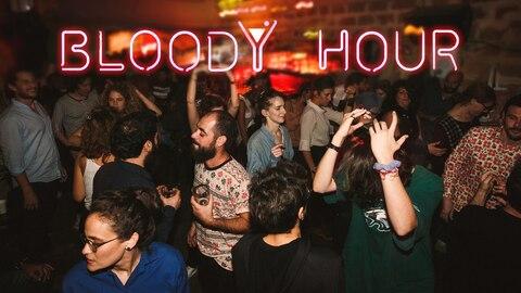 """Über tanzenden Menschen in einem Club ist eine rosa Neonschrift """"Bloody Hour"""" zu sehen"""