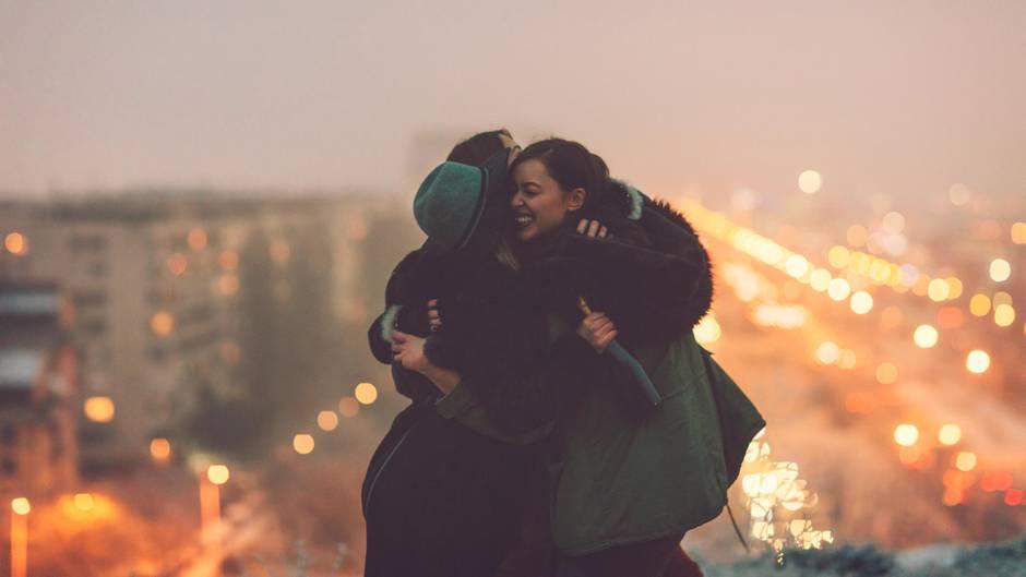 Drei Freundinnen stehen auf einer Brücke und umarmen sich
