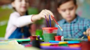 Zwei Kinder sitzen am Tisch und basteln