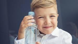 Ein Junge hält seine Trinkflasche und grinst