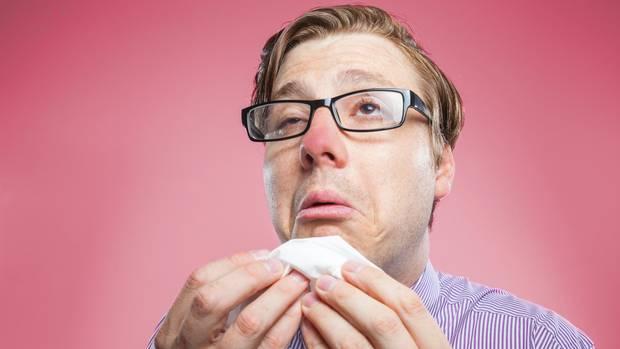 Ein erkälteter Mann putzt sich die Nase.