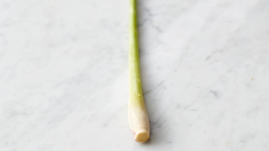 Das Zitronengras auf der Arbeitsfläche weich klopfen und von der harten äußeren Blattschicht befreien.