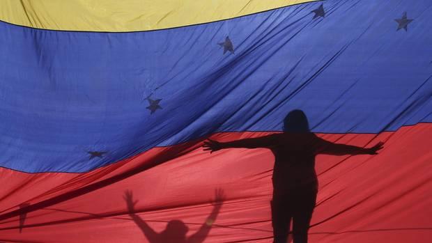 Protestanten hinter einer Flagge von Venezuela