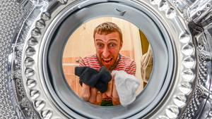 Ein Mann blickt in eine Waschmaschinentrommel