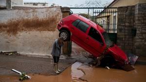 Eine Frau steht im griechischen Mandra vor einem von den Überschwemmungen beschädigten Auto
