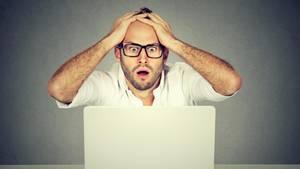 Ein man schaut entsetzt seinen Computer an und schlägt die Hände über dem Kopf zusammen