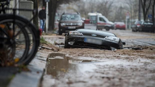Nach dem Wasserrohrbruch ist die Straße abgesackt und hat ein Auto zur Hälfte in die Tiefe gerissen