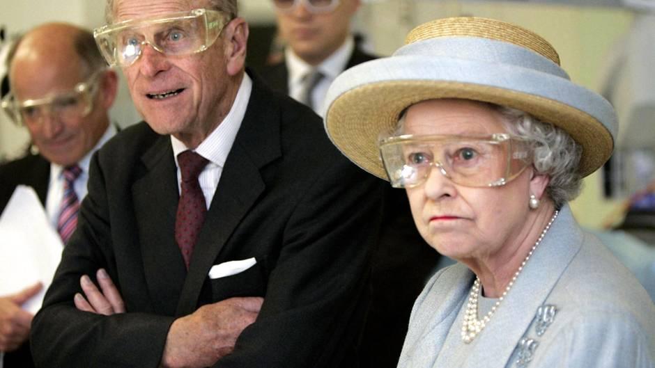 Queen Elizabeth II steht im himmelblauen Kostüm und oassendem Strohhut mit einer durchsichtigen Schutzbrille in einem Labor