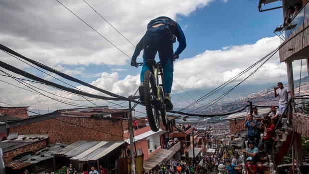Medellin, Kolumbien. Anwohner verfolgen massenhaft den Mountainbike-Fahrer, der während eines Rennens bergab durch die Gassen der Stadt rast.