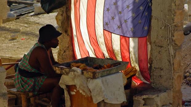 Frau sitzt in Port-au-Prince neben einer Flagge der USA