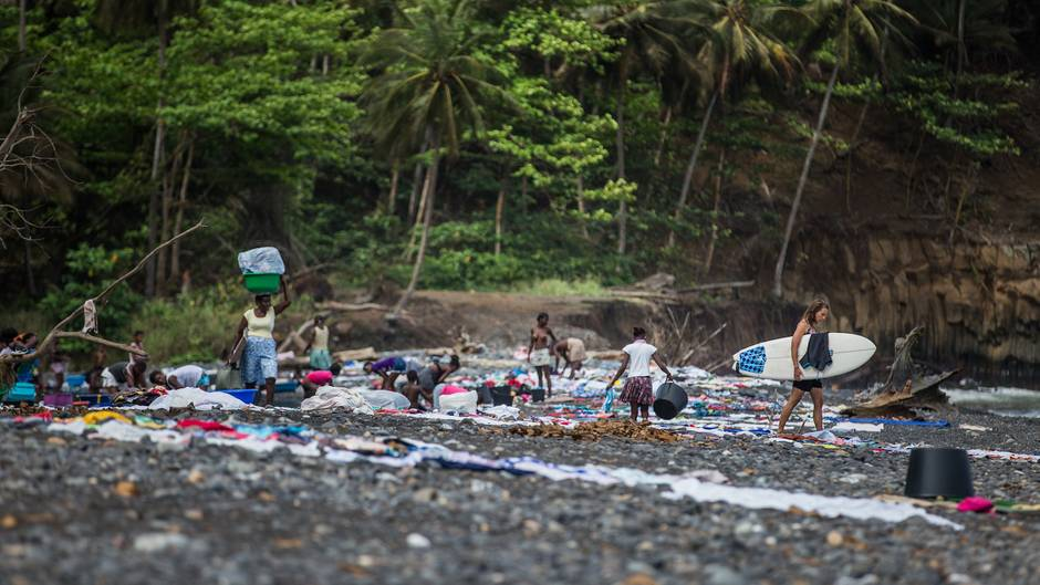 Frauen waschen ihre Wäsche in einem Fluss in der Nähe des Dorfs Agua Ize. Die nasse Wäsche wird anschließend auf den schwarzen, heißen Steinen am Strand von Praia Ize zum Trocknen ausgelegt.
