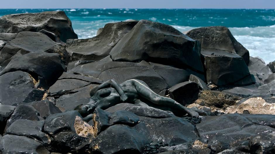 Eine schwarz bemalte Frau liegt auf schwarzen Felsen