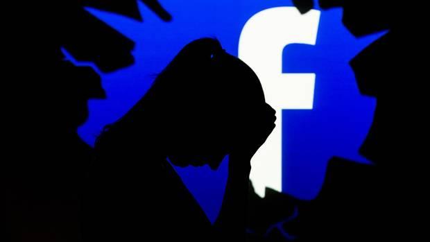 Der Schattenriss einer besorgten Frau ist vor dem Facebook-Logo zu sehen