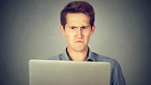 Ein Mann schaut irritiert auf seinen Laptop-Bildschirm