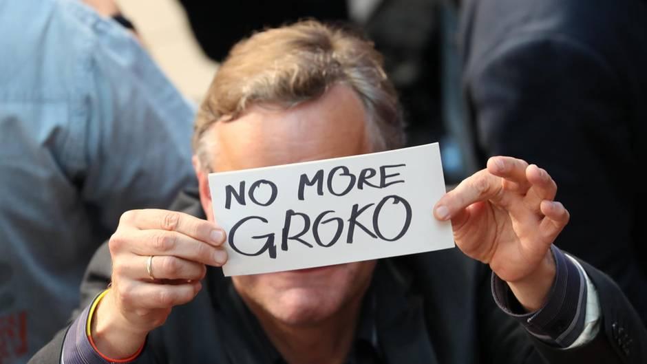 """Ein Mann hält auf der SPD-Wahlparty ein Schild mit der Aufschrift """"No More GroKo"""" vors Gesicht"""