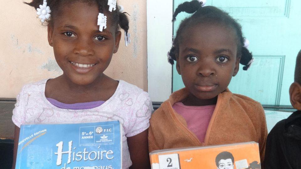 Die Mädchen freuen sich über ihre neuen Schulbücher