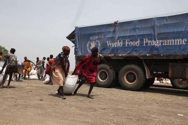 Von einer Sammelstelle schleppen Frauen 50-Kilo-Säcke mit Hirse nach Hause