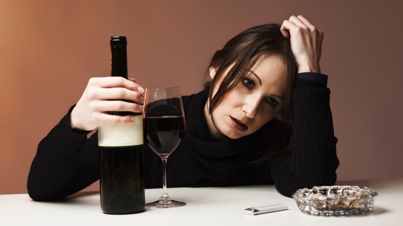 Eine traurige Frau trinkt Wein, während sie traurige Musik hört