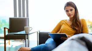 Eine junge Frau sitzt mit ihrem Tablet auf der Couch