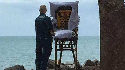 Ein letzter Blick aufs Meer: Ein Mitarbeiter des Queensland Ambulance Service mit der Patientin