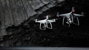 Zwei Drohnen des Modell Drohne DJI Phantom 4 Pro + schweben vor einer schwarzen Felswand