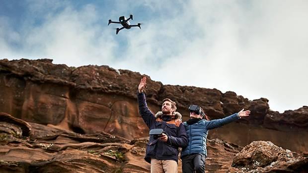 Ein paar winkt vor einer Felswand der Drohne Parrot Bebop 2 FPV zu. Die Frau trägt eine VR-Brille