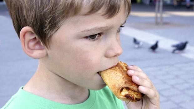 Ein kleiner Junge isst ein Gebäckstück
