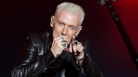 H.P. Baxxter von Scooter steht auf der Bühne und singt. Mit der rechten Hand hält er sich ein Mikrofon vor den Mund