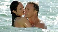 Daniel Craig badet als James Bond im Meer und hält dabei eine brünette Frau in den Armen