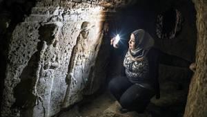 Im Schein ihres Handys hockt eine Frau mit Kopftuch vor einem steinernen Relief und betrachtet zwei gemeißelte Figuren