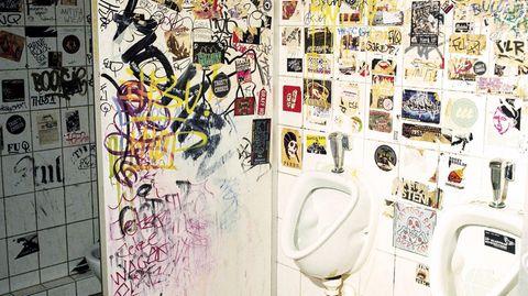 Eine öffentliche Männertoilette beklebt mit Aufklebern