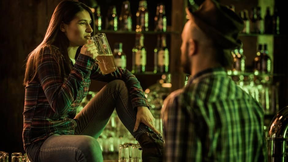 Eine Frau trinkt nachdenklich ein Bier in einer Bar