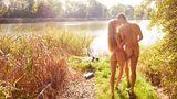 Ein blonder Mann und eine blonde Frau stehen nackt an einem See und küssen sich