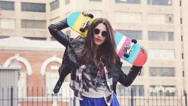 Eine junge Frau mit Sonnenbrille trägt ein Skateboard
