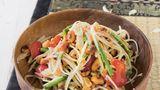 Som Tam – grüne-Papaya-Salat aus Thailand      Zutaten:    500 g grüne Papaya (aus dem Asia-Laden), 5 EL Erdnüsse, 3 große Knoblauchzehen, 3–4 Thai-Chili-Schoten (nach Belieben mehr), 3 EL getrocknete kleine Shrimps (aus dem AsiaLaden), 100 g Schlangenbohnen, Salz, 150 g Cocktailtomaten, 4 EL Fischsauce, plus mehr zum Abschmecken, 2 EL Limettensaft, plus mehr zum Abschmecken, 2 EL Palmzucker, plus mehr zum Abschmecken      Zubereitung:    Klassisch werden alle Zutaten für den Papaya-Salat in einem sehr großen Mörser miteinander vermischt.  Wer keinen sehr großen Mörser hat, stampft am besten die kleinen Zutaten miteinander und mischt die Masse anschließend in einer Schüssel mit den Papaya-Raspeln.        Die Papaya schälen, Fäden und Kügelchen in der Mitte entfernen und das Fruchtfleisch in lange dünne Streifen raspeln. Die Erdnüsse in einer Pfanne ohne Fett rösten, bis sie Farbe annehmen und beiseitestellen. Den Knoblauch abziehen und fein hacken. Die Chilischoten waschen, abtupfen und mit dem Knoblauch in einem großen Mörser zerreiben. Die getrockneten Shrimps zugeben und mit dem Stößel grob zerkleinern. Die Schlangenbohnen putzen, in mundgerechte Stücke schneiden und in Salzwasser etwa 3 Minuten blanchieren. Abgießen und mit der Hälfte der Erdnüsse im Mörser verarbeiten, die Bohnen aber nur leicht zerdrücken.        Die Cocktailtomaten waschen, trockentupfen, halbieren und im Mörser leicht zerdrücken, bis Saft austritt.        Alles in eine Schüssel umfüllen, mit Fischsauce, Limettensaft und Palmzucker würzen und alles vermischen. Vorsichtig die Papaya-Raspeln untermischen. Bei Bedarf nochmals mit Fischsauce, Palmzucker oder Limettensaft nachwürzen und mit den restlichen Erdnüssen anrichten.