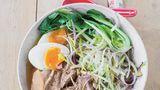 Ramen-Nudeln mit Schweineschulter, weichem Ei und Pak Choi      Zutaten für 4 Personen:  2 Karotten, 1 Stange Lauch, 1/4 Knolle Sellerie, 1 große Zwiebel, 400 g Schweineknochen (vom Metzger), 500 g Schweineschulter, 1 Kombu-Alge (etwa 10 x 10 cm aus dem Asialaden) 5 cm frischer Ingwer, in Scheiben geschnitten, 5 Knoblauchzehen, abgezogen, 4 Eier, 2 Frühlingszwiebeln, 2 EL Miso-Pasta, 3 EL Sojasauce, Salz, 400 g Ramen-Nudeln, 4 kleine Pak Choi, 150 g frische Sojasprossen, Chilipulver zum Bestauben        Zubereitung:  Karotten, Lauch und Sellerie putzen, in grobe Stücke schneiden, die Zwiebel samt der Schale halbieren. Mit Knochen und Schweineschulter in 3 l kaltem Wasser zum Kochen bringen. Eventuell entstehenden Schaum abschöpfen und die Temperatur reduzieren, sodass die Brühe nur noch leicht vor sich hin köchelt. Kombu-Alge, Ingwer und Knoblauch zugeben und alles etwa 2 Stunden köcheln lassen, bis die Schweineschulter zart ist. Das kann je nach Fleisch variieren.  Währenddessen die Eier 7 Minuten kochen und kalt abschrecken. Die Frühlingszwiebel putzen und der Länge nach in dünne Streifen schneiden.  Wenn das Fleisch weich ist, die Brühe durch ein Sieb abgießen. Die Miso-Paste in die Brühe rühren, mit Sojasauce und Salz abschmecken. Das Fleisch in Scheiben schneiden und in der Brühe warm halten.  Die Ramen-Nudeln nach Packungsangabe in Salzwasser weich kochen und abgießen. Den Pak Choi putzen, halbieren und kurz vor dem Servieren in die heiße Brühe zum Fleisch geben.  Zum Servieren Nudeln, Pak Choi, Fleisch und die halbierten Eier in tiefen Schalen anrichten. Brühe angießen, Sojasprossen und Frühlingszwiebel darauf verteilen und nach Belieben mit Chilipulver bestauben.