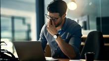 Ein Mann mit Brille sitzt vor dem Laptop und massiert sich die Nase