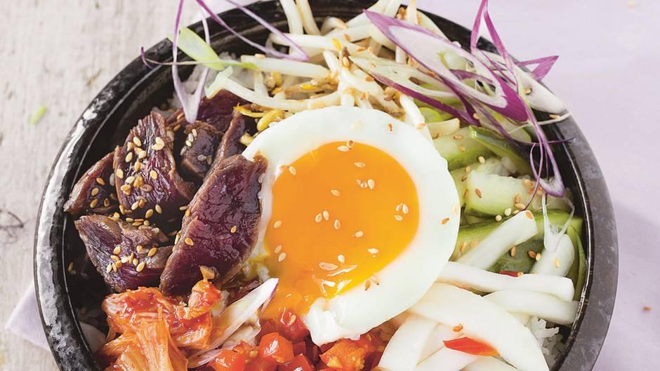 Bibimbap: koreanische Bowl        Zutaten:    Für das Fleisch und die Marinade: 2 Knoblauchzehen, 3 EL Sojasauce, 1 EL Honig, 1 EL Sesamöl, 1 TL Sesamsaat, 250 g Lendensteak vom Rind,     Für das Gemüse: 1/3 Salatgurke, 1 TL Sesamöl, 2 EL Reisessig, Salz, 2 Mairübchen oder 1/2 weißer Rettich, 1 Chilischote, gehackt, 2 EL Weißweinessig, 1 EL Sonnenblumenöl Für den Kimchi: 200 g Chinakohl, Salz, 1 TL brauner Zucker, 1 EL Sojasauce, 1 EL Chilipaste,     Außerdem: 250 g Basmati-Reis, 1 rote Paprikaschote, 1 Knoblauchzehe, 1 Frühlingszwiebel, 3 EL Sonnenblumenöl, Salz, 2 Handvoll Sojasprossen, 4 Eier        Zubereitung:    Für die Rindfleisch-Marinade die Knoblauchzehen abziehen und hacken. Mit Sojasauce, Honig, Sesamöl sowie Sesamsaat vermengen und das Rindfleisch in einem Plastikbeutel oder einer Schüssel über Nacht darin marinieren.    Für das Gemüse die Gurke waschen und in mundgerechte Stücke schneiden. Mit Sesamöl, Reisessig und 1/2 TL Salz über Nacht marinieren. Die Mairübchen schälen und in dicke Stifte schneiden. Mit Chili, 1/2 TL Salz, Weißweinessig und Sonnenblumenöl mischen, über Nacht marinieren. Für den schnellen Kimchi den Chinakohl putzen und mundgerecht schneiden. Mit 1 EL Salz, dem braunen Zucker, Sojasauce und Chilipaste gut durchkneten. Mindestens über Nacht durchziehen lassen.    Am Zubereitungstag den Reis mit der doppelten Menge Wasser bissfest garen. Währenddessen die Paprika waschen, abtupfen, von Stielsatz sowie Samen befreien und würfeln, den Knoblauch abziehen und hacken, die Frühlingszwiebel putzen und dünn schneiden.    In einer Pfanne 1 EL Öl erhitzen. Paprika und Knoblauch darin kurz scharf anbraten, salzen und warm stellen.    Anschließend die Sojasprossen scharf anbraten, salzen und ebenfalls warm stellen.  Das Fleisch aus der Marinade nehmen, auf jeder Seite scharf anbraten und aufschneiden. In einer zweiten Pfanne im übrigen Öl die Spiegeleier braten. Alles miteinander anrichten.