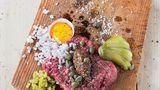 Beef Tatar      Zutaten:    600 g Rinderschulter, 2 Schalotten, 8 Essiggurken, 1 EL Worcester-Sauce, Fleur de Sel, frisch gemahlener schwarzer Pfeffer, 4 Eigelb, 2 EL Kapern aus dem Glas, 2 EL grober Senf,    Außerdem: glatte Petersilie für die Dekoration, frisches Bauernbrot      Zubereitung:  Für das Tatar das frische Fleisch sofort zubereiten und unverzüglich verzehren. Von Silberhäuten, Sehnen und Fett befreien. Zunächst in dünne Scheiben, dann in Streifen und feine Würfel schneiden und zum Schluss hacken.        Die Schalotten abziehen und fein würfeln. Die Hälfte der Gurken ebenfalls fein würfeln und die anderen Gurken dünn auffächern.        Zum Servieren aus dem Fleisch entweder einen großen oder vier kleine, gleich große Laibe formen und auf einem Holzbrett platzieren. Mit Worcester-Sauce beträufeln und mit Salz und Pfeffer würzen. Eigelb (Serviervorschlag: in halben Eierschalen), Zwiebelwürfel, Gurkenwürfel, Gurkenfächer, Kapern und Senf dazu anrichten. Die Petersilie waschen, trockenschütteln, die Blätter abzupfen und das Brett damit dekorieren.    Dazu passt frisches Bauernbrot.