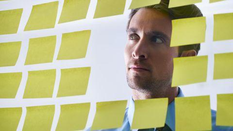 Ein Mann blickt durch ein Fenster, das voller Post-its klebt