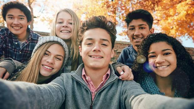 Sechs Jugendliche posieren für ein Selfie.
