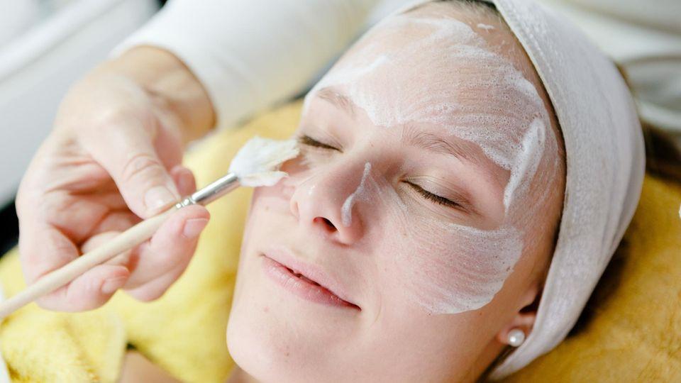 Eine Frau bekommt ein Fruchtsäurepeeling beim Hautarzt
