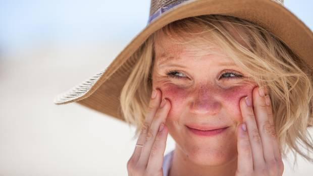 Eine Frau mit Sonnenhut cremt sich mit Sonnencreme die Wangen ein
