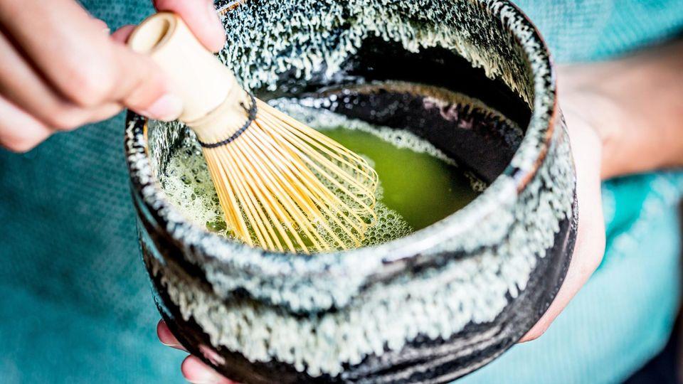 Eine Frau bereitet Öl mit Matchapulver für eine Augenmaske zu